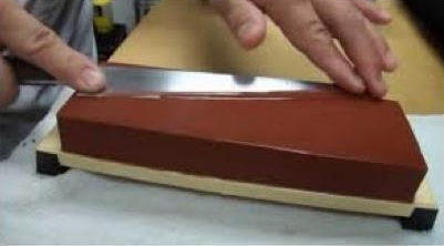 Person sharpening knife with flat whetstone